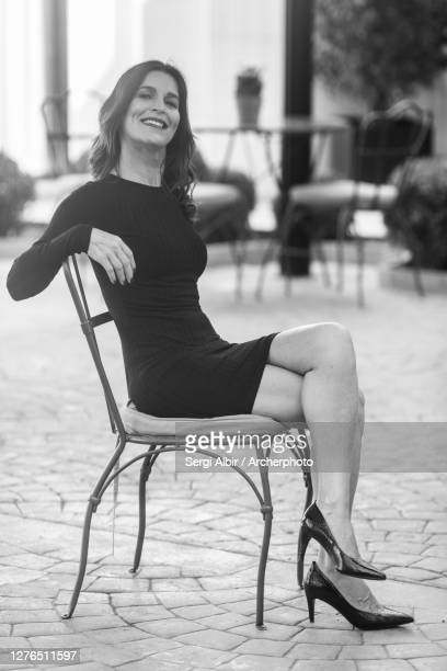 middle-aged woman in a black dress sitting and smiling - sergi albir fotografías e imágenes de stock