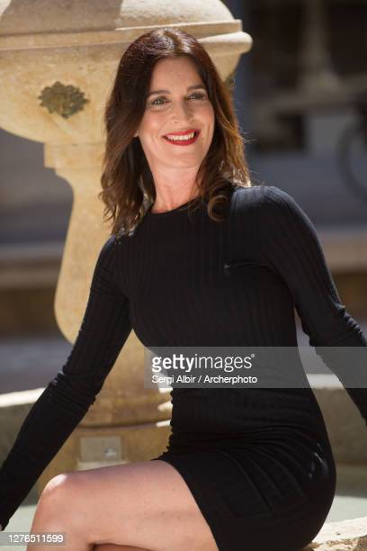 middle-aged woman in a black dress sitting on a fountain and smiling - sergi albir fotografías e imágenes de stock