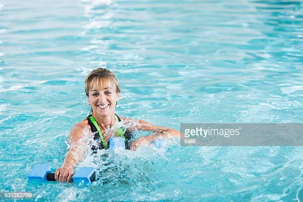 Moyenne ans Femme faisant gymnastique aquatique dans la piscine
