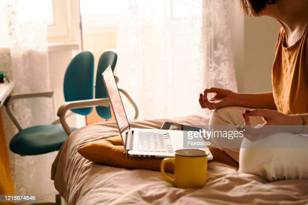 a middle-aged woman in white jeans and a yellow sweater sitting on the bed in a yoga pose in front of a laptop and a cup of coffee - working from home stock pictures, royalty-free photos & images