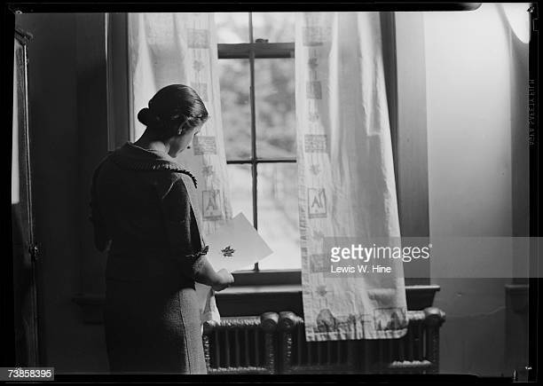 A middleaged woman looks at a piece of paper with a leaf print on it as she stands at a curtained window by a radiator in a classroom USA early 20th...