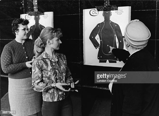 Middle-aged woman points to a shooting target in a indoor gun range while two women stand by and watch, Dearborn, Michigan, 1967 or 1968. The younger...