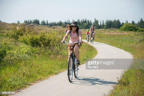 Middle-aged woman ride bicycle on a country road near Skagen, Denmark
