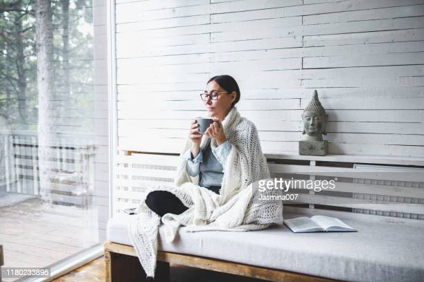 middle-aged woman siting comfortable and enjoys tea - mindfulness stock pictures, royalty-free photos & images