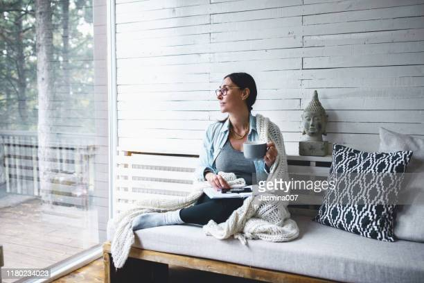 middle-aged woman siting comfortable and enjoys tea - zen like stock pictures, royalty-free photos & images