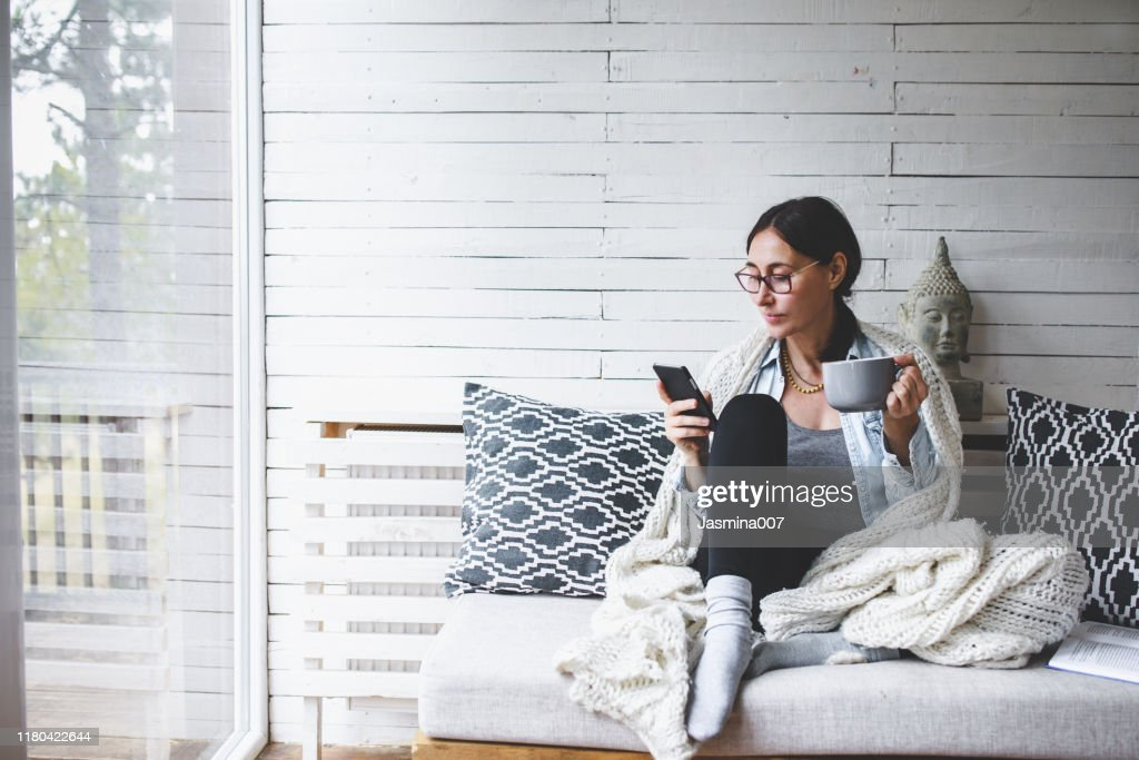 Middle-aged woman siting comfortable and enjoys tea : Stock Photo
