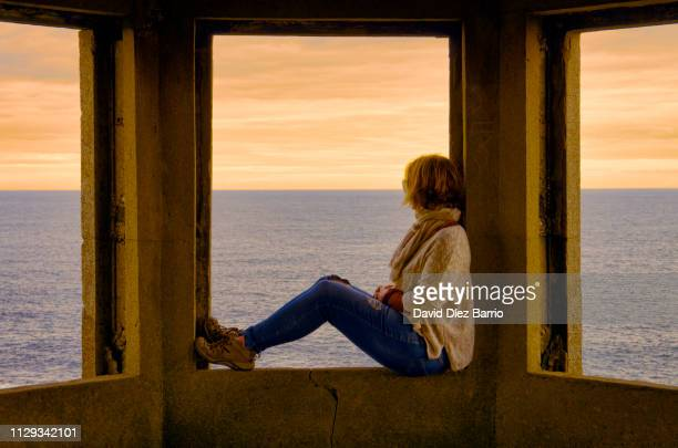 middle-aged woman sitting in a window enjoying sunset in the irish sea - symmetry stock pictures, royalty-free photos & images