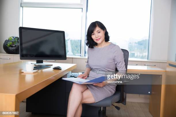 middle-aged woman sitting in the office began her work