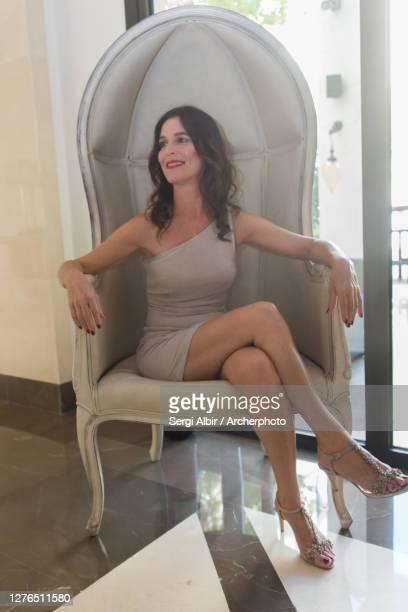 middle-aged woman sitting on a big armchair - sergi albir fotografías e imágenes de stock