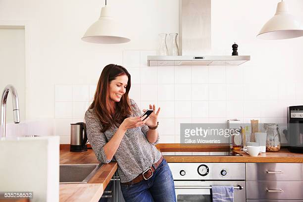middle-aged woman texting on her smartphone - 40 49 jaar stockfoto's en -beelden