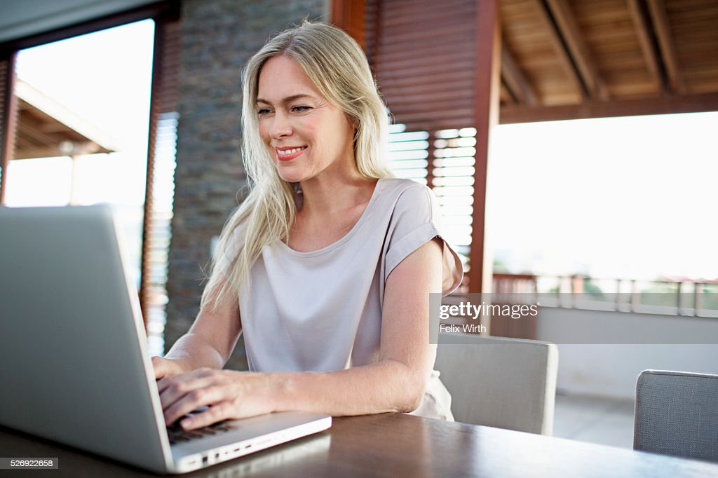 Middle-aged woman using laptop at home : Stockfoto