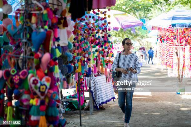 Middle-aged woman walking through art market and looking at colorful merchandise, Sayulita, Mexico