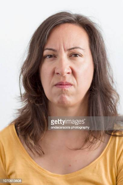 a middle-aged woman with an expression of worry and disgust - disappointment stock pictures, royalty-free photos & images