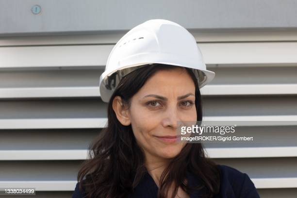 middle-aged woman with dark hair and helmet in front of a power plant, freiburg, baden-wuerttemberg, germany - sigrid gombert stock pictures, royalty-free photos & images