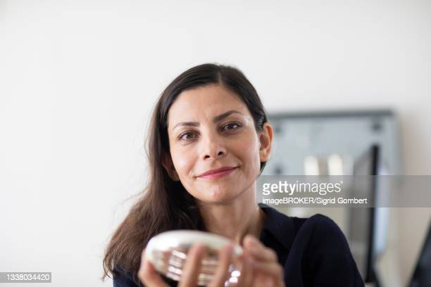 middle-aged woman with dark hair checks product at work, freiburg, baden-wuerttemberg, germany - sigrid gombert fotografías e imágenes de stock