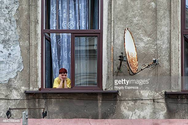 Middle-aged woman with short purple hair staring bored throughout the window of an old block, with satelite tv plate on her right side.