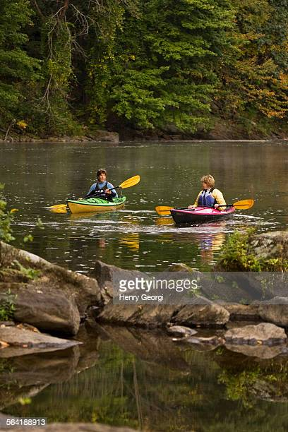2 middle-aged women sea-kayak on Farmington River near Collinsville, Connecticut, USA.