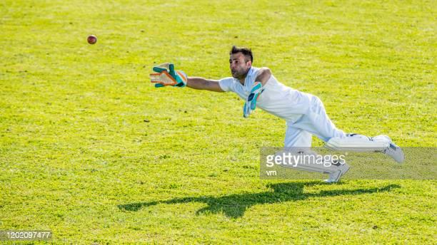 midden-oosten cricket speler probeert om de bal te vangen - cricket player stockfoto's en -beelden