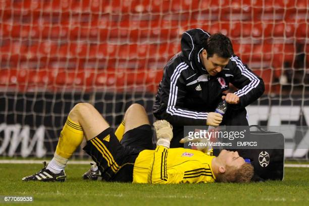 Middlesbrough goalkeeper Connor Ripley lies on the ground as he is treated by their physiotherapist
