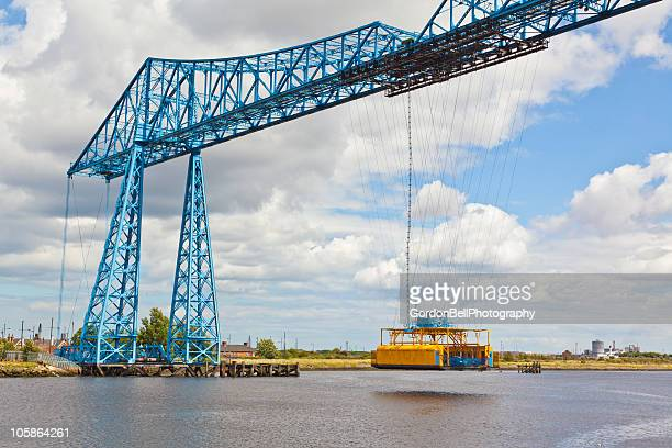 The bridge connects Middlesbrough on the south bank of the River to Port Clarence on the north bank. It is a transporter bridge, carrying a moving cradle or gondola suspended from the bridge, across the river in 90 seconds. The gondola can carry 200 people, 9 cars or 6 cars and one minibus.