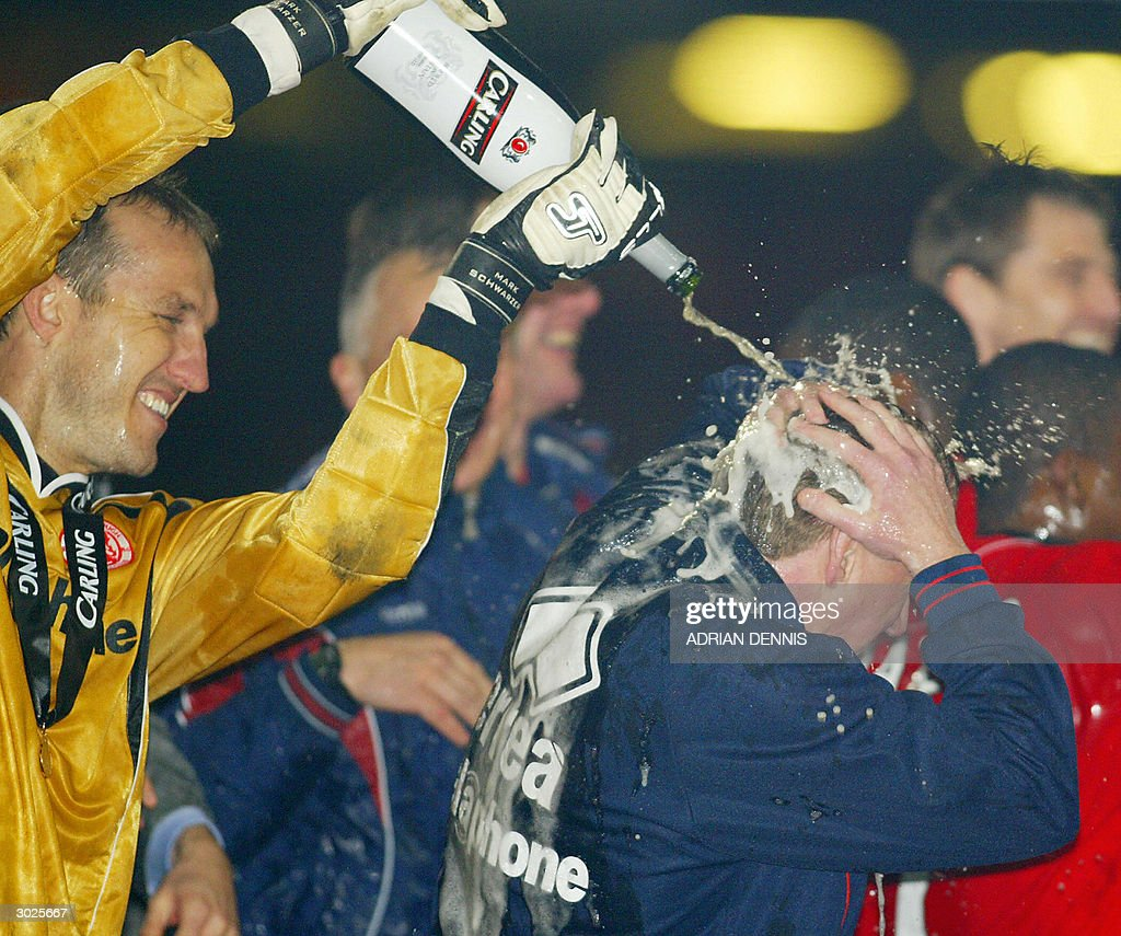 Middlesbrough's goal keeper Mark Schwarzer (L) soaks his team's coach Steve McClaren with champaigne as they celebrate winning the Carling Cup Final football match against Bolton 29 February, 2004 in Cardiff, Wales. Middlesbrough defeated Bolton 2-1.