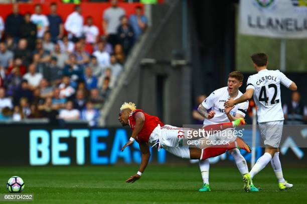 Middlesbrough's Spanish midfielder Adama Traore falls under a challenge from Swansea City's English defender Alfie Mawson during the English Premier...