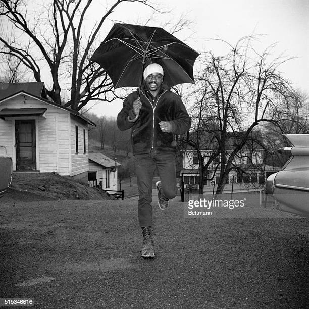 Middleweight boxer Rubin Carter protected from rain by huge umbrella gets in a little roadwork at his training camp here February 10th Carter is...