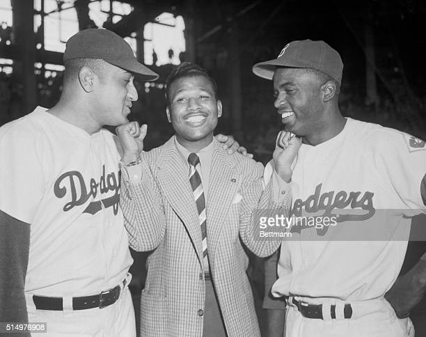 Middleweight Champ Sugar Ray Robinson called on a pair of Dodger Champs at Ebbet's Field today to bestow love pats with his championship fists for...