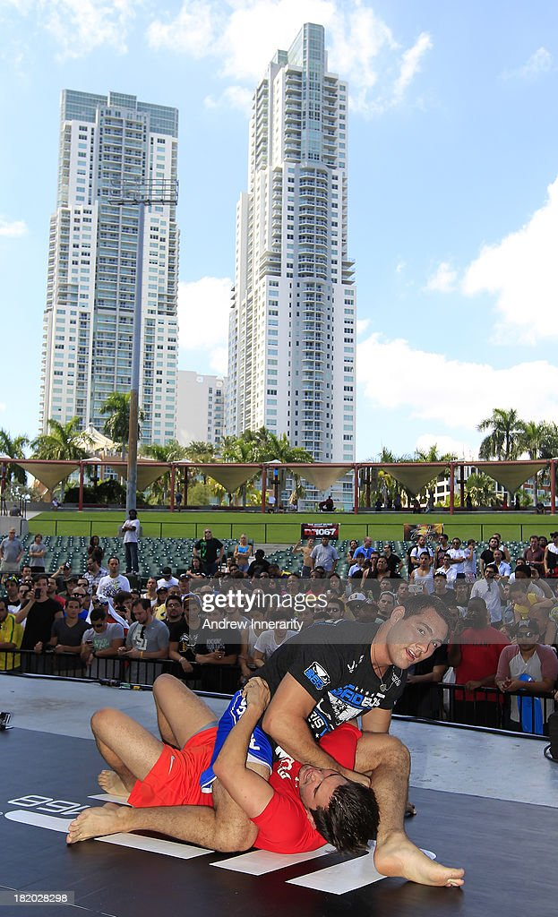 UFC middleweight champion Chris Weidman (top) grapples with his sparring partner Randell Aleman (bottom) during the UFC 168: Weidman v SIlva 2 press tour at Klipsch Amphitheater at Bayfront Park on September 27, 2013 in Miami, Florida.