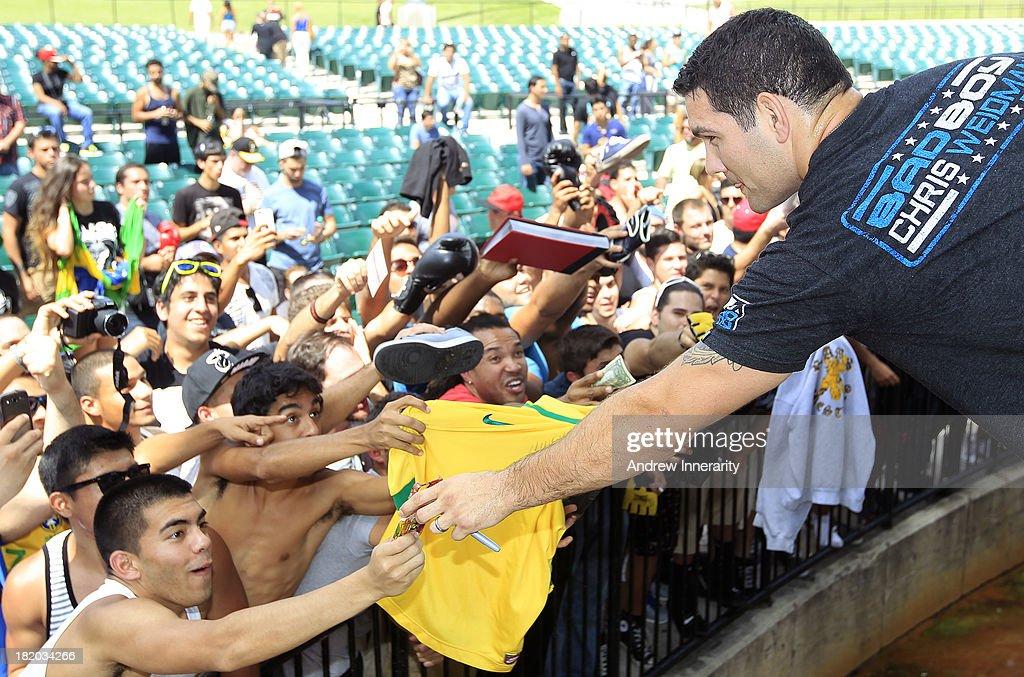 UFC middleweight champion Chris Weidman signs autographs during the UFC 168: Weidman v SIlva 2 press tour at Klipsch Amphitheater at Bayfront Park on September 27, 2013 in Miami, Florida.