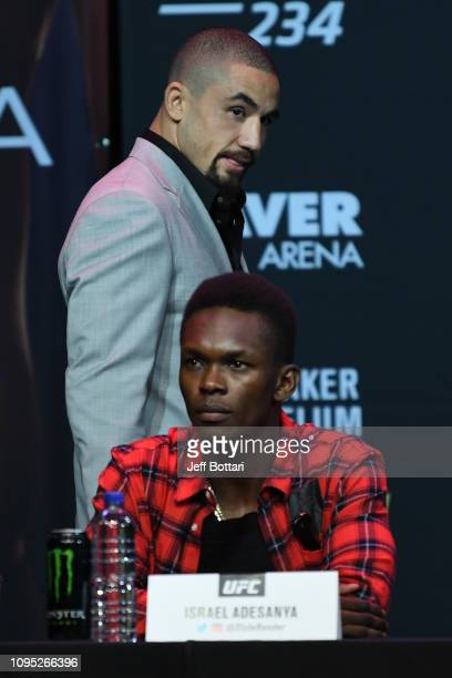 UFC middleweight champion Robert Whittaker of Australia walks onstage past Israel Adesanya during the UFC 234 Press Conference inside The Palms at...