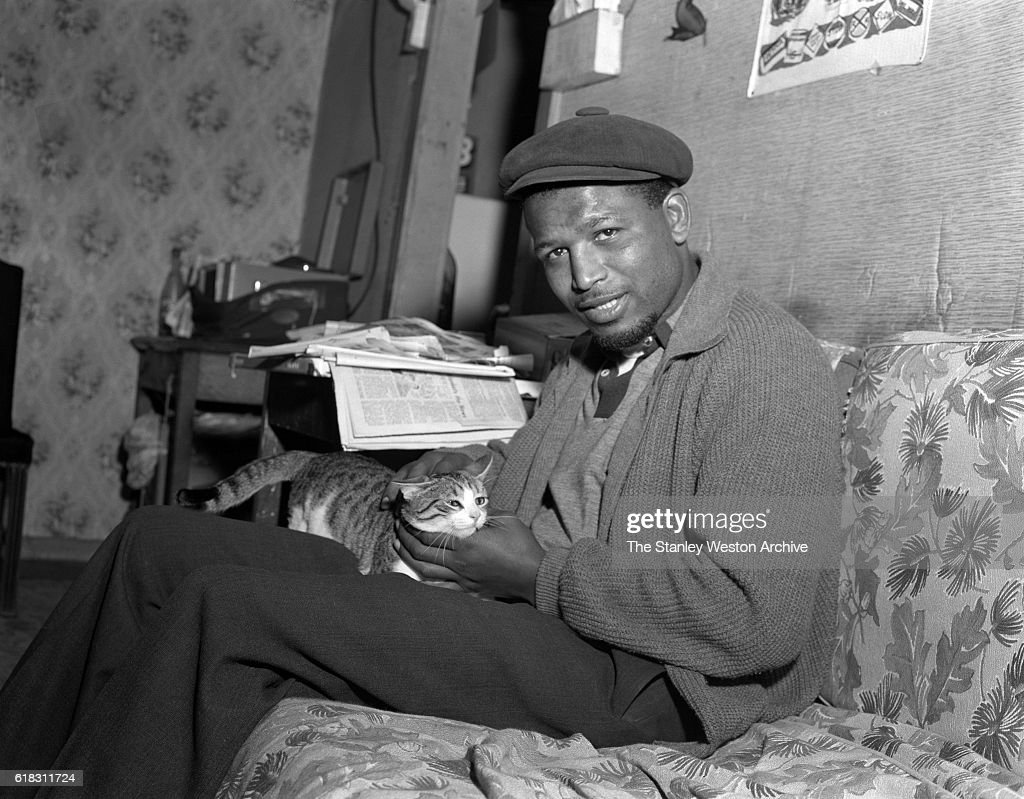 Middleweight champion Sugar Ray Robinson spends some time with his pet cat in Greenwood Lake, New York, November 3, 1956.