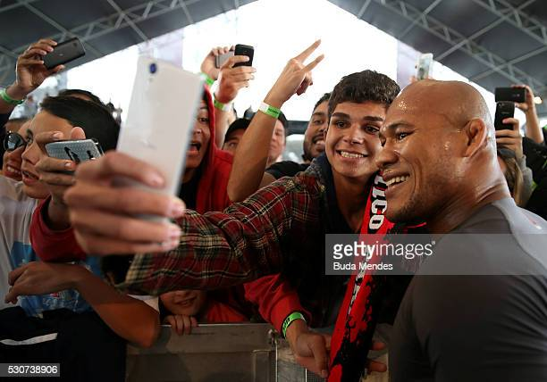 Middleweight contender Ronaldo 'Jacar�� Souza of Brazil takes photos with fans during an open training session at Arena da Baixada stadium on May 11...