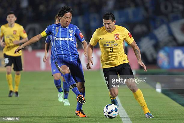 Midfield Yasuhito Endo of Gamba Osaka fights for the ball against forward Elkeson de Oliveira Cardoso of Guangzhou Evergrande during the semi finals...