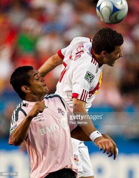 Midfielder Amado Guevara of the Toronto FC leaps for the ball with midfielder Luke Sassano of the New York Red Bulls during the match at BMO Field...