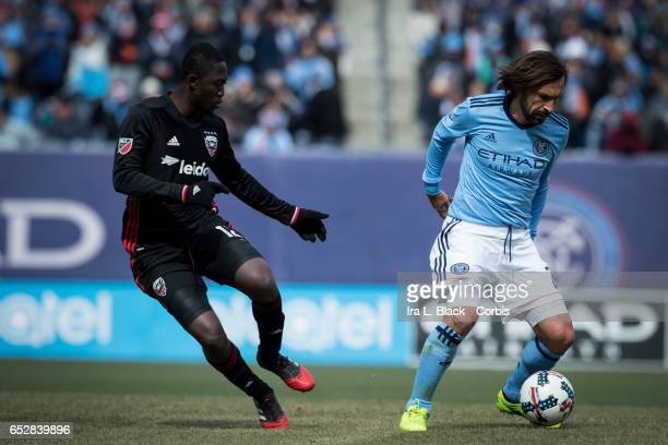 Midfielder Andrea Pirlo of New York City FC spins to avoid Patrick Nyarko during the 2017 MLS Season Opening match between NYCFC vs DC United on...