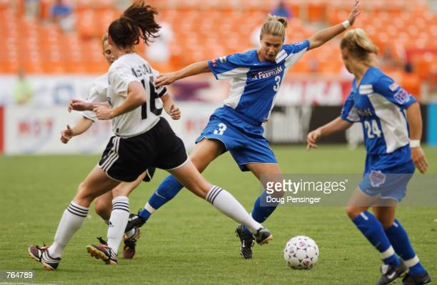 Midfielder Ann Cook of the Washington Freedom gains control of the ball against Christine McCann of the Boston Breakers defends during the WUSA match...