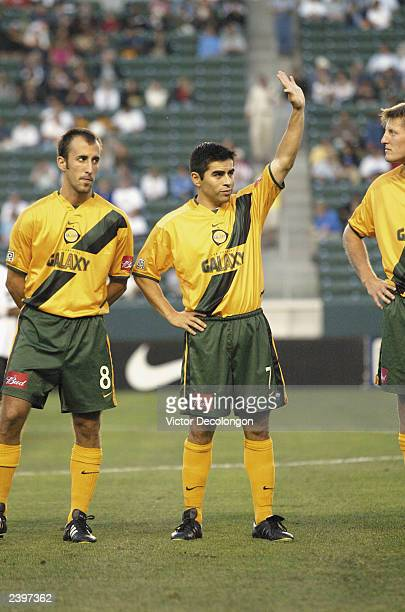 Midfielder Antonio Martinez of the Los Angeles Galaxy waves to the crowd during player introductions as teammate Peter Vagenas looks prior to the MLS...