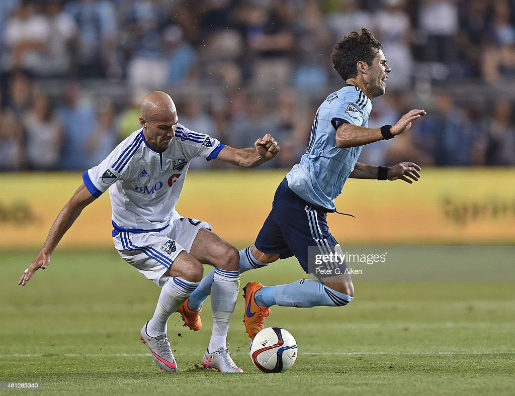 Mid-fielder Benny Feilhaber #10 of Sporting Kansas City gets tripped up by defender Laurent Ciman #23 of the Montreal Impact during the second half on July 18, 2015 at Sporting Park in Kansas City, Kansas.