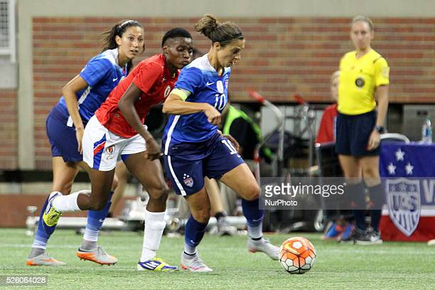US midfielder Carli Lloyd carries the ball up the field under the pressure of Haiti defender Roselord Borgella chased by US forward Christen Press in...