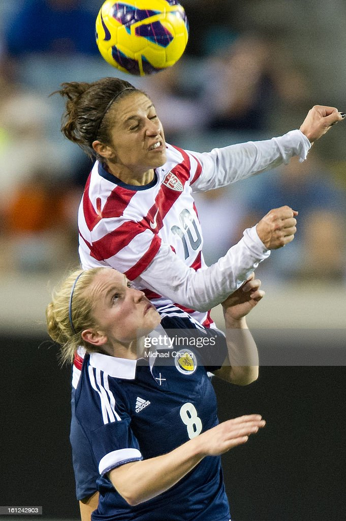 Midfielder Carli Lloyd #10 of the United States leaps over midfielder Kim Little #8 of Scotland to head a ball at EverBank Field on February 9, 2013 in Jacksonville, Florida. The United States defeated Scotland 4-1.
