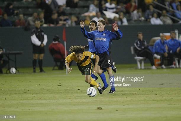 Midfielder Cobi Jones of the Los Angeles Galaxy trips and falls while being pressured by midfielder Arturo Alvarez and midfielder Richard Mulrooney...