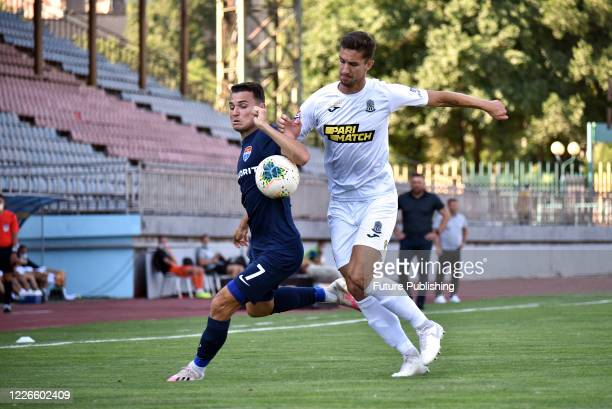 Midfielder Dmytro Topalov of FC Mariupol and defender Dmytro Lytvyn of FC Olimpik Donetsk are seen in action during the Ukrainian Premier League...
