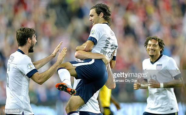 Midfielder Graham Zusi jumps into the arms of teammate Matt Besler ,and celebrates with Brad Evans and Jermaine Jones , after his goal against...