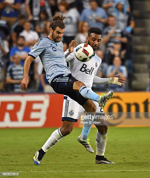 Midfielder Graham Zusi of Sporting Kansas City battles for the ball against forward Giles Barnes of the Vancouver Whitecaps FC during the second half...