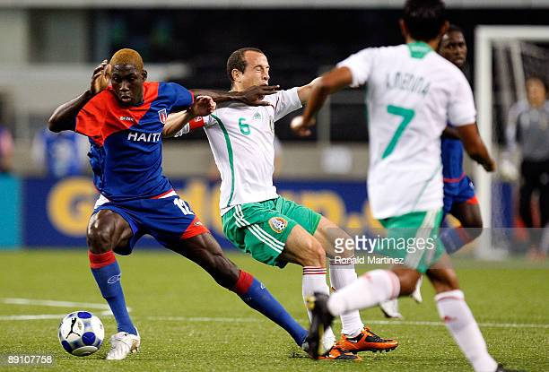 Midfielder James Marcelin of Haiti dribbles the ball past Gerardo Torrado of Mexico during the CONCACAF Gold Cup Quarterfinals at Dallas Cowboys...