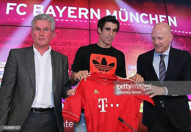 Midfielder Javi Martinez presents his new number alongside head coach Jupp Heynckes and sport director Matthias Sammer of Bayern Munich during a...