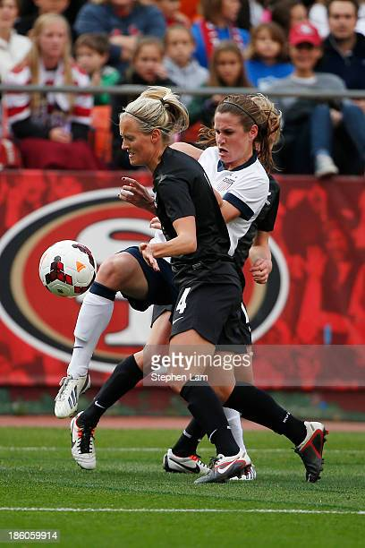 Midfielder Katie Hoyle of New Zealand battles for the ball with midfielder Heather O'Reilly of the US Women's National Team during the first half of...