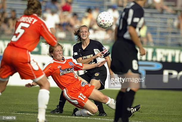 Midfielder Krista Davey of the New York Power shoots the ball as midfielder Michelle French of the San Jose CyberRays defends during their WUSA game...