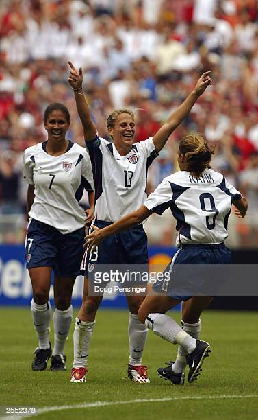 Midfielder Kristine Lilly of the United States celebrates her first period goal as she is joined by teammates forward Mia Hamm and midfielder Shannon...